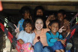 Jacqueline with the village kids at Prey Kabas taking shelter from the rain during a video shoot